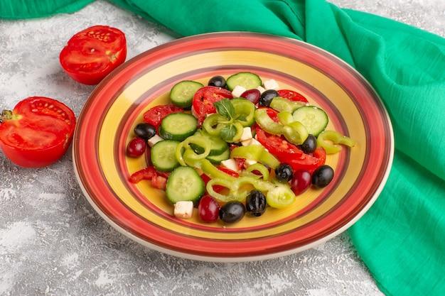 Salada de legumes fresca de vista frontal com pepinos fatiados, tomates, azeitona e queijo branco dentro do prato com tomates na superfície cinza comida de vegetais salada refeição lanche