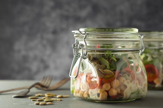 Salada de legumes fresca em frasco de vidro. dieta, desintoxicação, comer limpo e conceito do vegetariano, espaço da cópia.