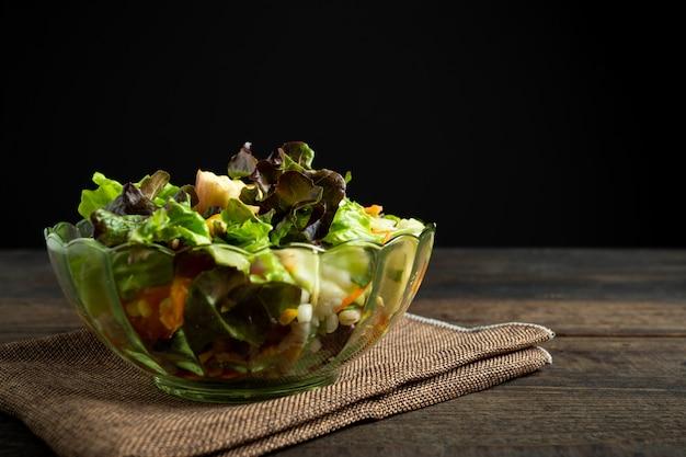Salada de legumes fresca em madeira.
