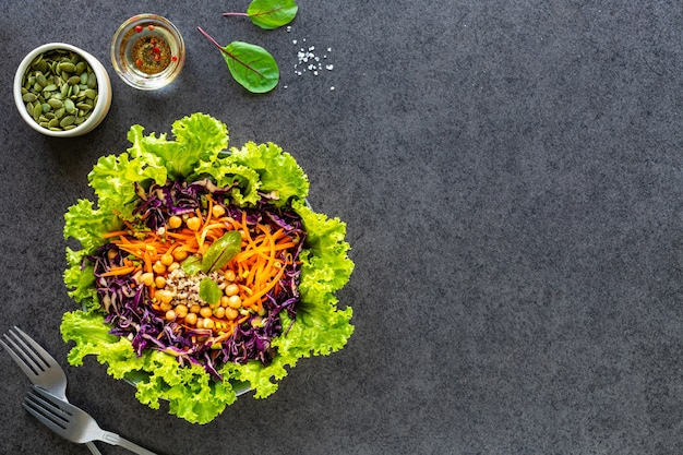 Salada de legumes fresca em um prato preto. vista do topo