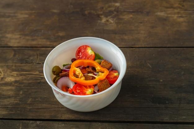 Salada de legumes fresca em uma saladeira em uma mesa de madeira.
