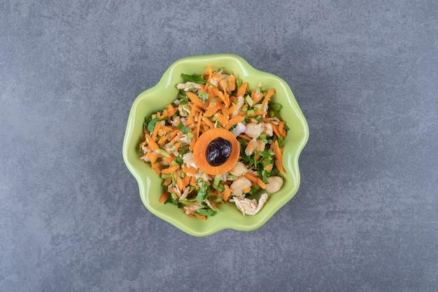 Salada de legumes fresca em uma tigela verde.
