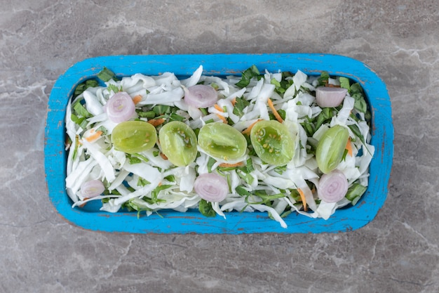 Salada de legumes fresca na placa azul.