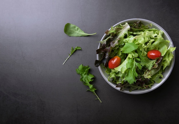 Salada de legumes fresca saudável com tomate, espinafre, alface no prato na mesa