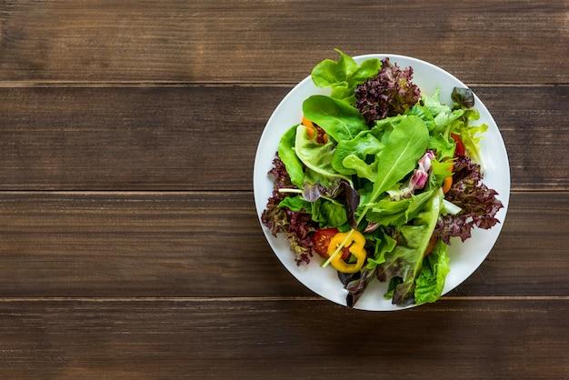 Salada de legumes fresca saudável mistura colorida no prato branco redondo