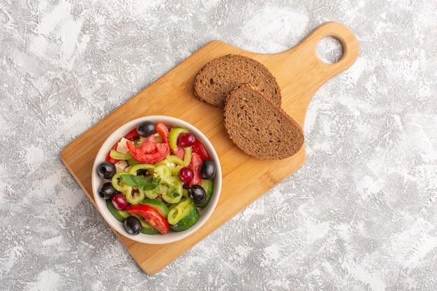 Salada de legumes fresca vista de cima com pepinos fatiados, tomates, azeitona e queijo branco dentro de um prato com pão na mesa cinza