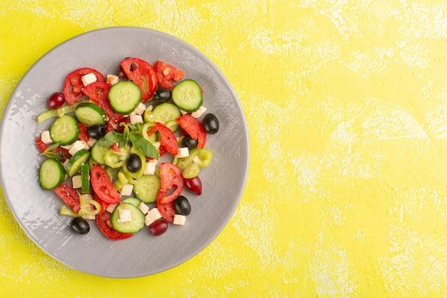 Salada de legumes fresca vista de cima com pepinos fatiados, tomates e azeitona dentro do prato na mesa amarela comida de vegetais salada refeição cor lanche