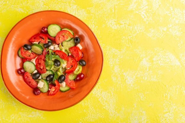 Salada de legumes fresca vista de cima com pepinos fatiados, tomates e azeitona dentro do prato no fundo amarelo foto colorida de refeição de salada de legumes