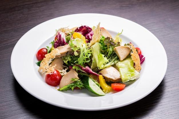 Salada de legumes frescos com carne de frango, coberta com óleo