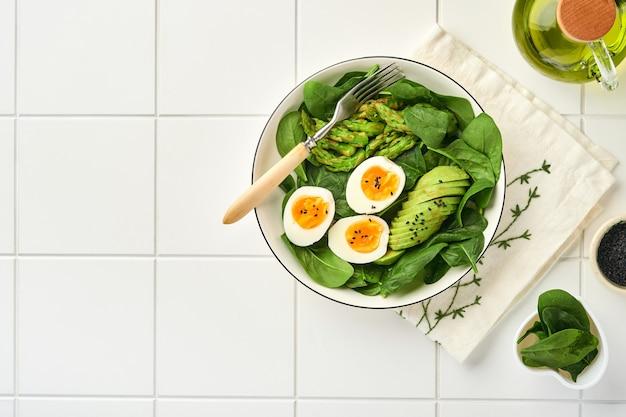 Salada de legumes frescos com espargos e abacate ovos amassados, sementes de gergelim preto e espinafre no prato