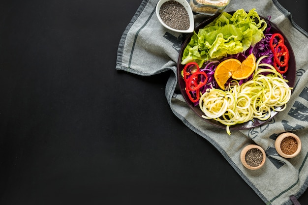 Salada de legumes frescos com ingredientes na toalha de mesa