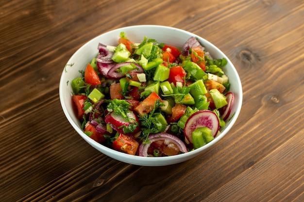 Salada de legumes frescos, incluindo pepinos fatiados, tomates vermelhos, cebola e outras coisas dentro da chapa branca na superfície rústica de madeira