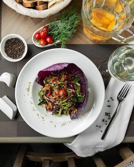 Salada de legumes grelhada na folha de couve roxa com ervas.
