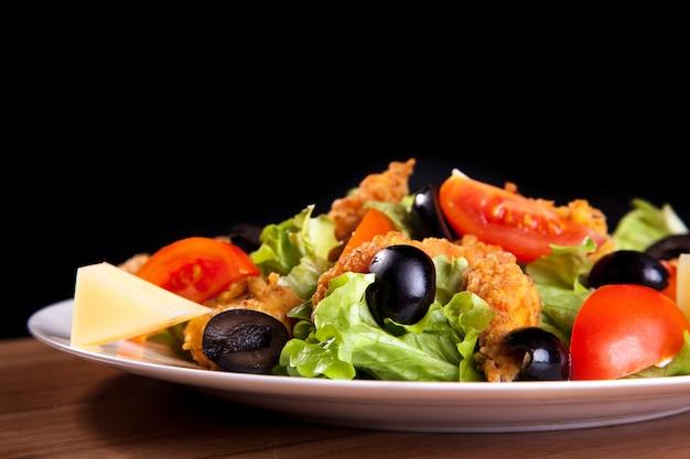 Salada de legumes mediterrânica com azeitonas de frango, queijo, tomate, verduras, sobre uma mesa de madeira e fundo preto.