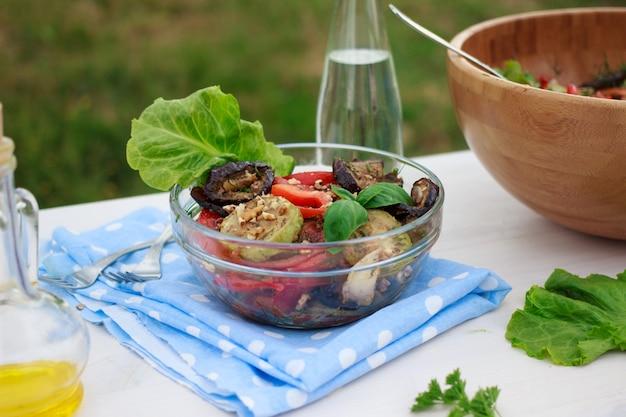 Salada de legumes mediterrânica saudável com beringelas grelhadas e abobrinhas ao ar livre no verão