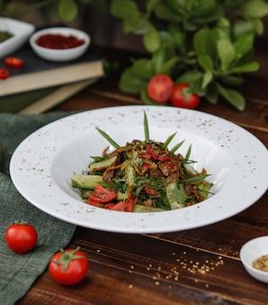 Salada de legumes mista com ervas dentro de um prato branco sobre uma mesa de madeira