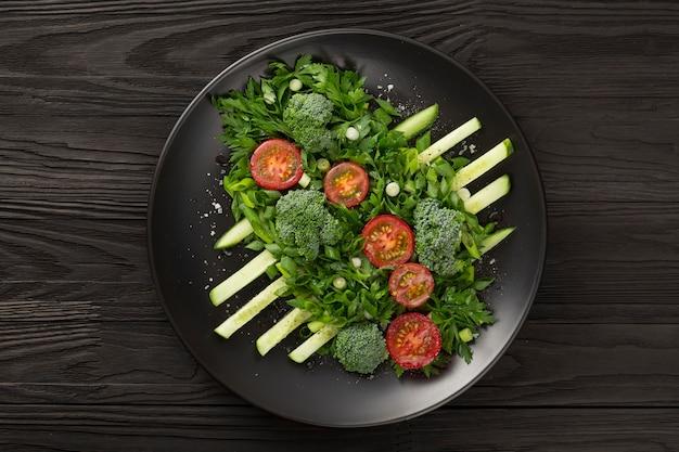 Salada de legumes na haute cuisine de design de prato escuro. foto em tom baixo