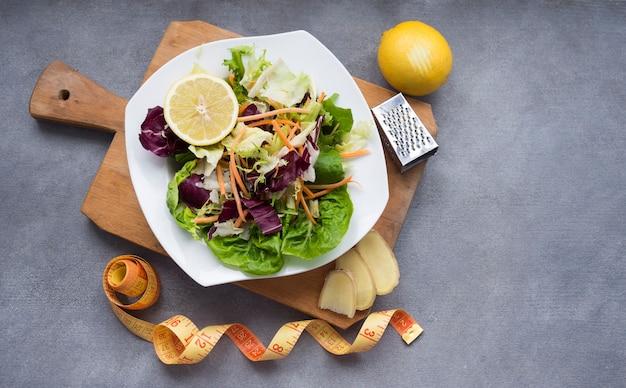 Salada de legumes na tábua de madeira com fita métrica