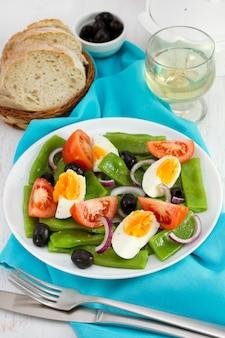 Salada de legumes no prato, pão e vinho branco