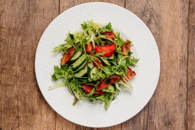 Salada de legumes no prato redondo branco na mesa de madeira. macro de cima.