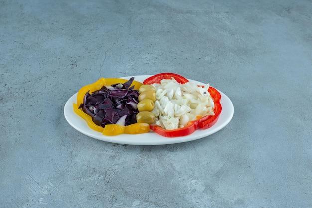 Salada de legumes picada em um prato branco.