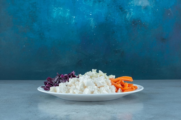 Salada de legumes picada em uma travessa branca.