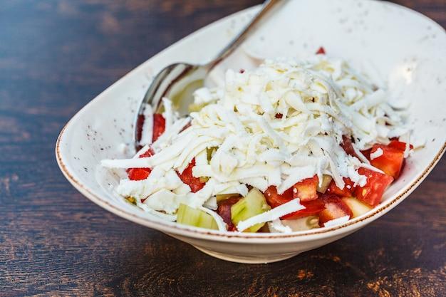 Salada de legumes prato nacional dos balcãs em um prato branco na mesa do restaurante.