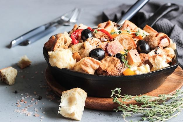 Salada de legumes quente com couve-flor assada, pimentão, champignon, azeitona e pão.