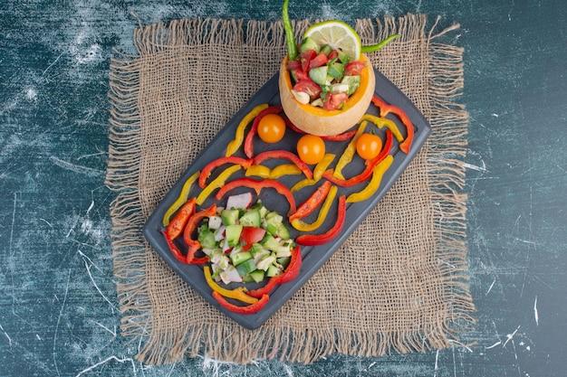 Salada de legumes sazonais com tomate cereja, pimentão, feijão verde e outros ingredientes.