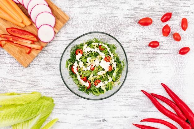 Salada de legumes verde em placa de vidro sobre a vista de cima da mesa