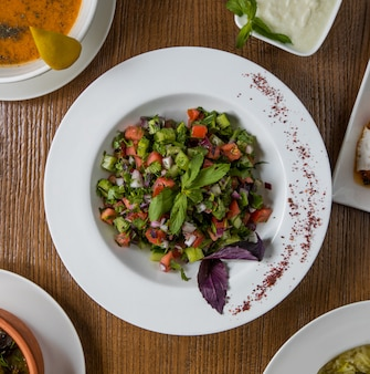 Salada de legumes verdes de vista superior com cubos dentro da placa branca.