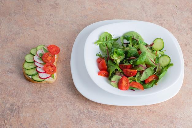 Salada de legumes verdes e tomate em um prato branco sobre a mesa. salada de vegetais primavera com um sanduíche de vegetais em um prato branco.