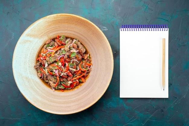 Salada de legumes vista de cima com carne fatiada dentro do prato, junto com o bloco de notas sobre o ingrediente de refeição alimentar de salada de fundo azul escuro