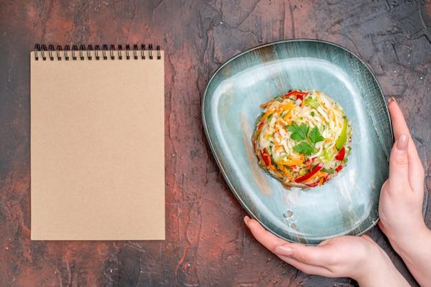 Salada de legumes vista de cima redonda em formato de prato na mesa escura