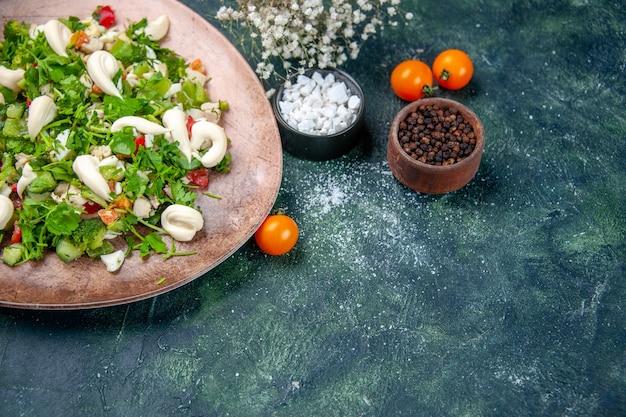 Salada de legumes vista frontal dentro de um prato elegante em fundo azul escuro