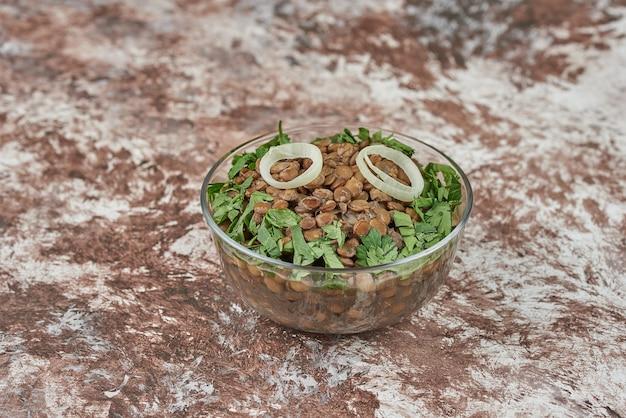 Salada de lentilha verde com ervas e cebola em um copo de vidro