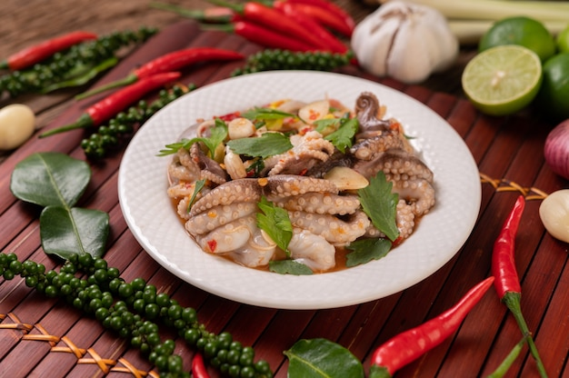 Salada de lula com coentro, cebola verde picada, alho e milho no prato