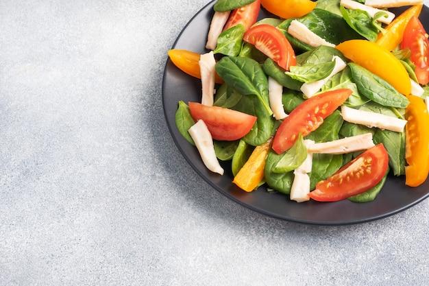 Salada de lula cozida, tomate fresco, folhas de espinafre. delicioso prato de dieta brilhante com legumes e frutos do mar. copie o espaço. vista do topo