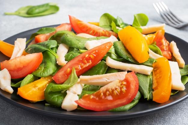 Salada de lula cozida, tomate fresco, folhas de espinafre. delicioso prato de dieta brilhante com legumes e frutos do mar.