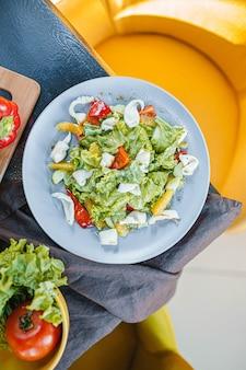 Salada de lula, tomate, pimenta e verduras em um close-up de prato