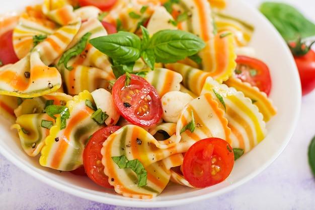 Salada de macarrão colorido farfalle com tomate, mussarela e manjericão.