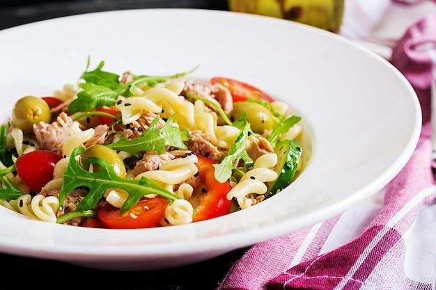 Salada de macarrão com atum, tomate, azeitonas, pepino, pimentão e rúcula no fundo rústico