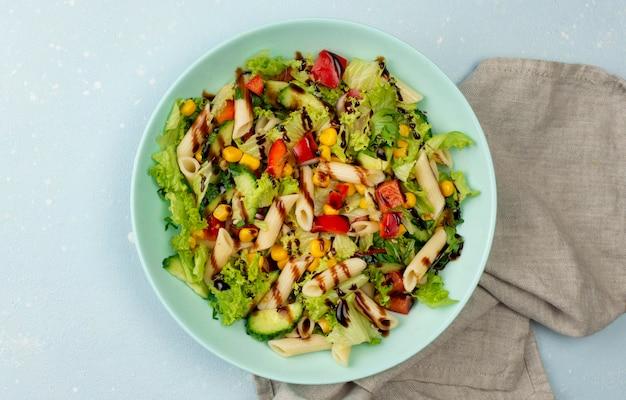 Salada de macarrão com vinagre balsâmico e toalha de cozinha vista de cima