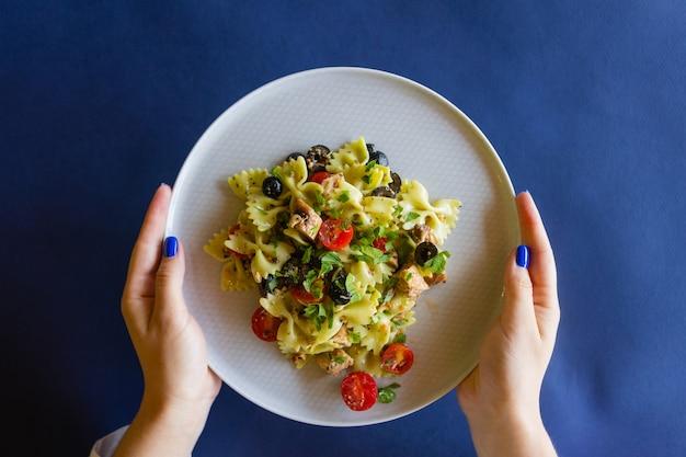 Salada de macarrão fusili, com pesto de rúcula, suculentos tomates, azeitonas e cebola.