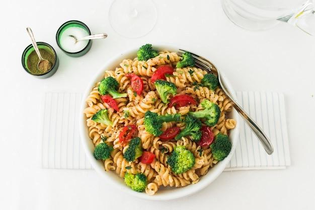 Salada de macarrão fusilli com tomate e brócolis no guardanapo