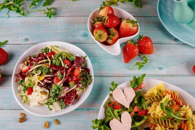 Salada de macarrão italiano com salsicha de coração e salada na mesa de madeira