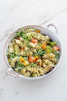 Salada de macarrão rotini com rúcula e tomate cereja, prato saudável de verão