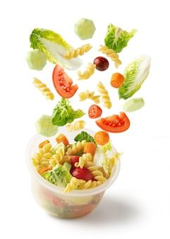 Salada de macarrão voando de recipiente