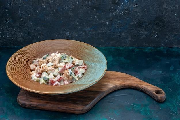 Salada de maionese com vegetais fatiados dentro de um prato na mesa azul escuro, salgadinhos com salada