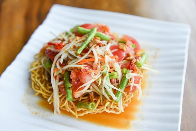 Salada de mamão apimentada em macarrão crocante no prato branco